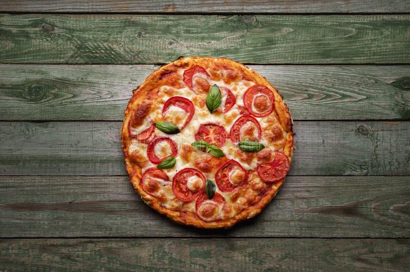 Pizza deliciosa con queso y tomates en la tabla de madera rústica fotografía de archivo