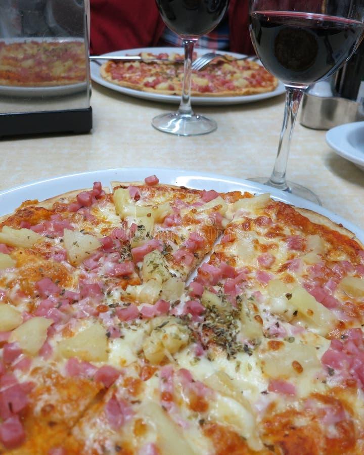Pizza deliciosa de Hawaian e um vidro do vinho tinto fotos de stock royalty free