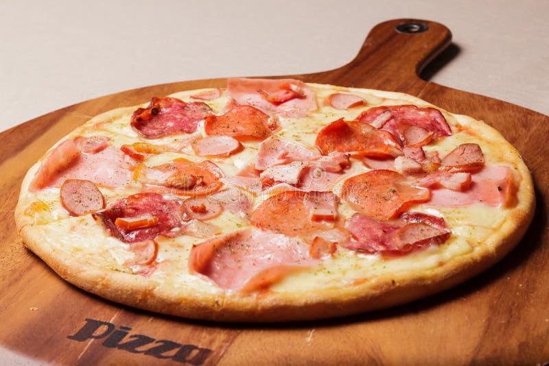 A pizza deliciosa serviu na placa de madeira - Imagen imagem de stock