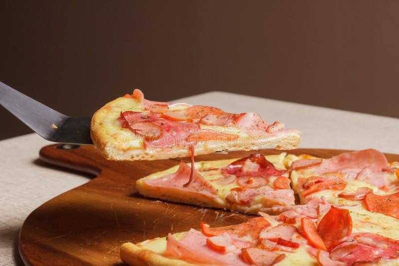 A pizza deliciosa serviu na placa de madeira - Imagen foto de stock