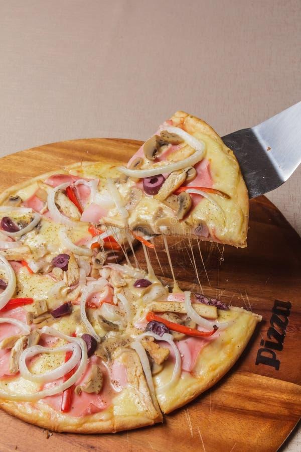A pizza deliciosa serviu na placa de madeira - Imagen imagens de stock royalty free