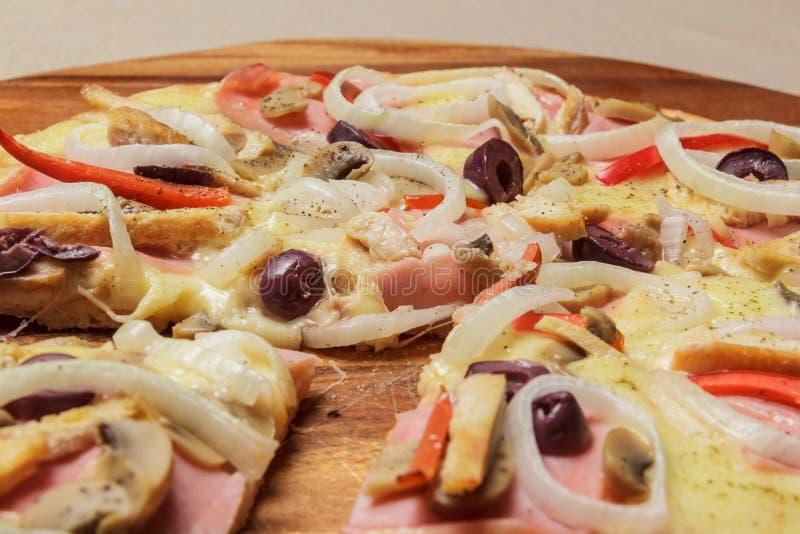 A pizza deliciosa serviu na placa de madeira - Imagen fotografia de stock