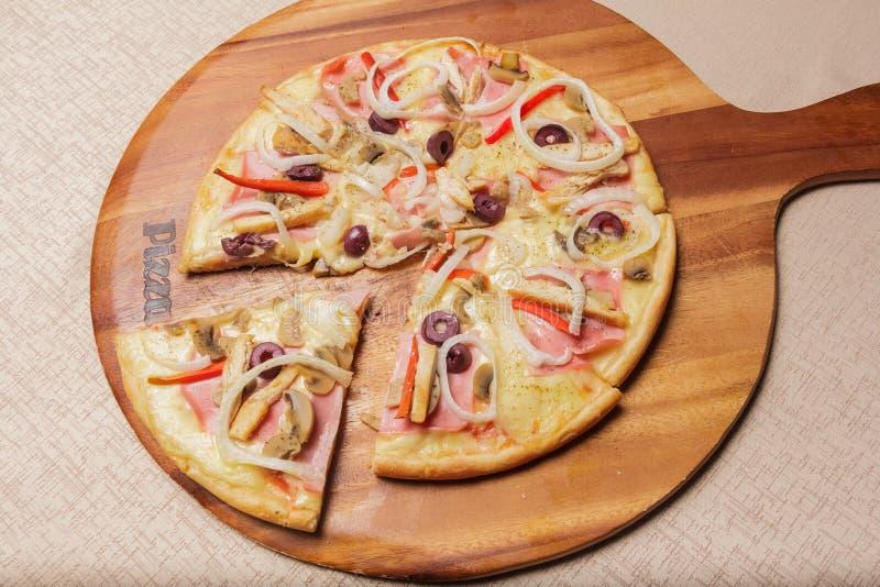 A pizza deliciosa serviu na placa de madeira - Imagen fotos de stock royalty free