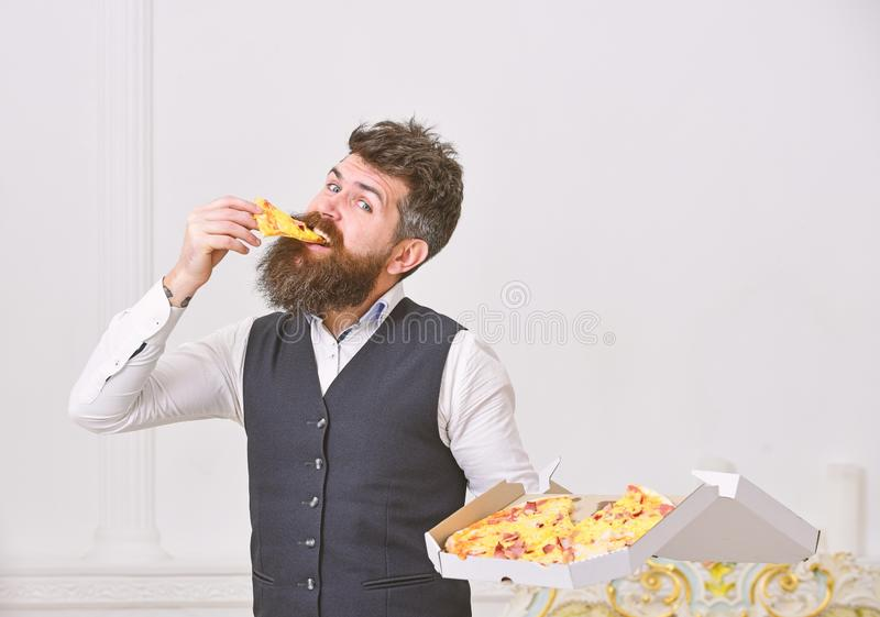 Pizza delivery concept. Macho in classic clothes hungry, holds slice of cheese pizza, eats, white background. Man with. Beard and mustache holds delivered box royalty free stock photos