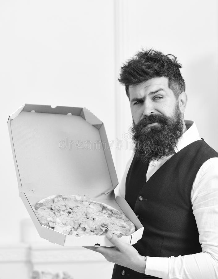 Pizza delivery concept. Macho in classic clothes hungry, on suspicious face, going to eat pizza, luxury interior. Background. Man with beard and mustache holds stock photography