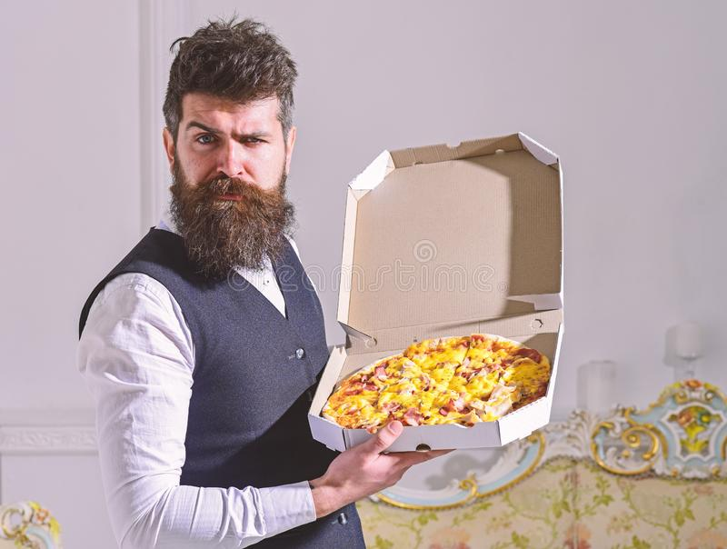 Pizza delivery concept. Man with beard and mustache holds delivered box with tasty fresh hot pizza. Macho in classic. Clothes hungry, on strict face, going to royalty free stock images