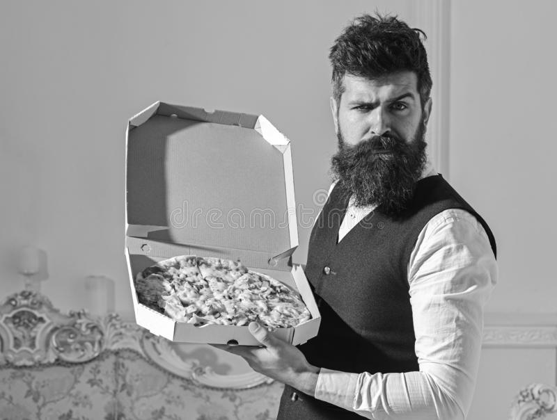 Pizza delivery concept. Man with beard and mustache holds delivered box with tasty fresh hot pizza. Macho in classic. Clothes hungry, on strict face, going to royalty free stock photos