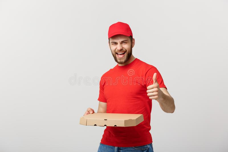 Pizza delivery concept. Young handsome delivery man showing pizza box and holding thumb up sign. Isolated on white. Background stock photos