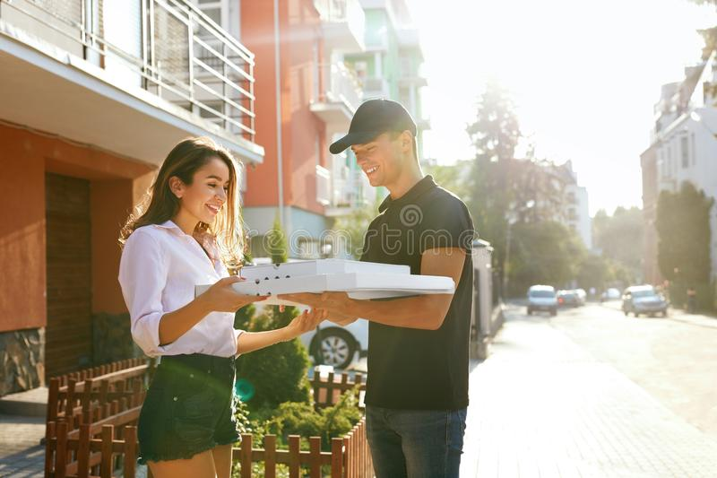 Pizza Delivery. Courier Giving Woman Boxes With Food Outdoors. Client Receiving Order. High Resolution royalty free stock image