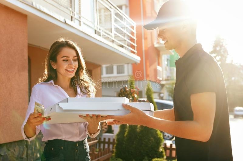 Pizza Delivery. Courier Giving Woman Boxes With Food Outdoors. Client Receiving Order. High Resolution stock photo