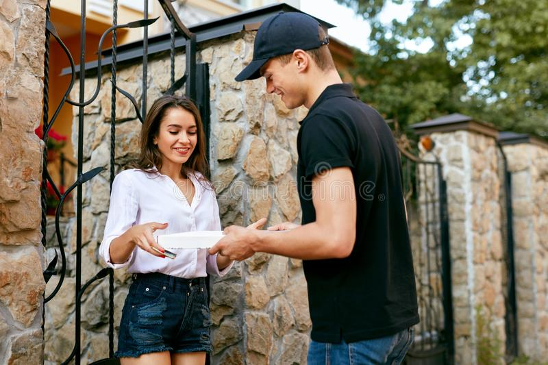 Pizza Delivery. Courier Giving Woman Boxes With Food Outdoors. Client Receiving Order. High Resolution stock photography