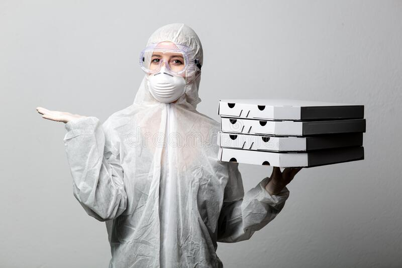 Pizza delivery girl in protective suit stock image