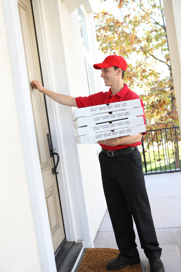 Pizza Delivery Man. A handsome young pizza delivery man holding a pizza royalty free stock photo