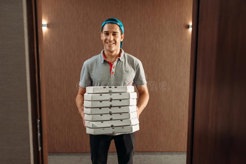 Pizza delivery man with boxes, delivering service. Courier from pizzeria holds cardboard package indoors stock photo