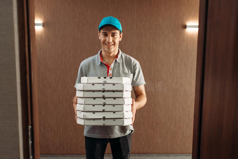 Pizza delivery man with boxes, delivering service. Courier from pizzeria holds cardboard package indoors royalty free stock photography