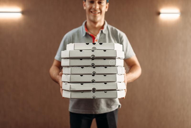 Pizza delivery man with boxes, delivering service. Courier from pizzeria holds cardboard package indoor royalty free stock photos