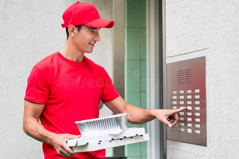 Pizza delivery man carrying boxes using the intercom. Pizza delivery man in red uniform carrying boxes using the intercom at door royalty free stock photos