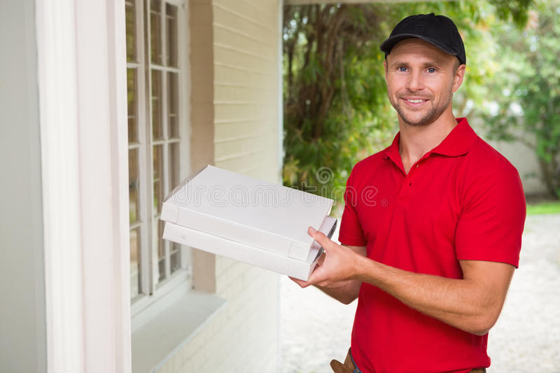 Pizza delivery man delivering pizzas. To a house stock image