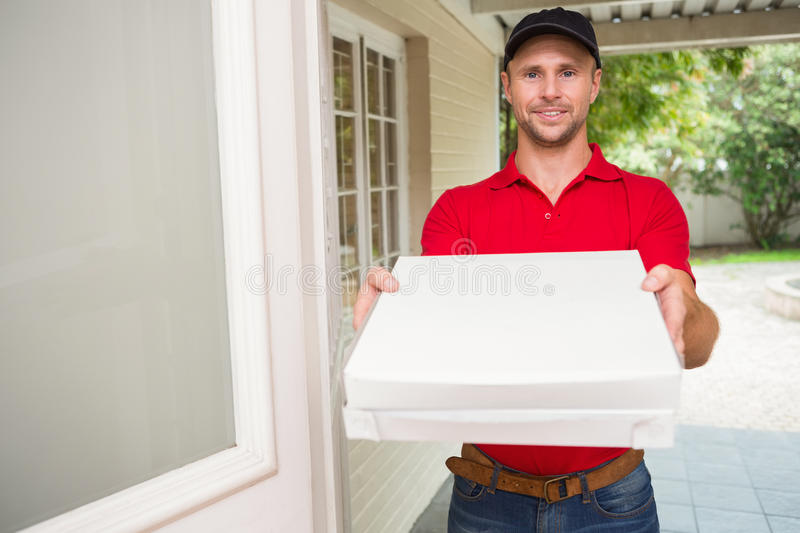 Pizza delivery man delivering pizzas. To a house royalty free stock photography