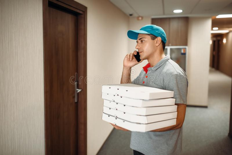 Pizza delivery man at the door calls to customer. Delivering service. Courier from pizzeria holds carton boxes and talk by phone indoors royalty free stock photo