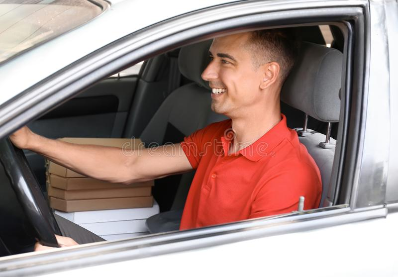 Pizza delivery man driving a car royalty free stock photos