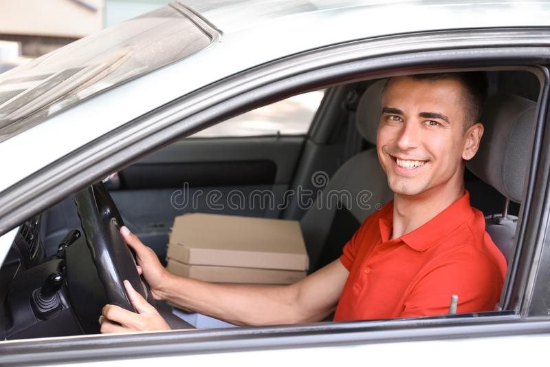 Pizza delivery man driving a car royalty free stock photography