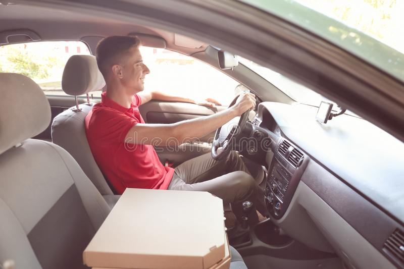 Pizza delivery man driving a car stock image
