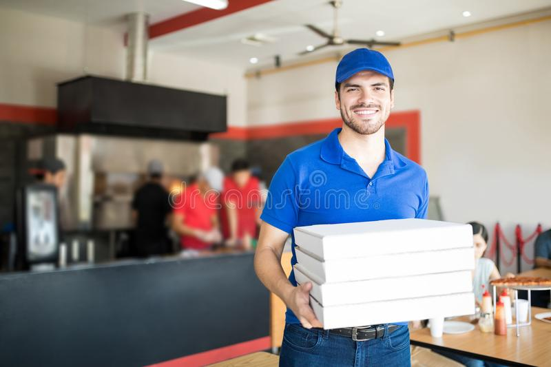 Pizza delivery man holding pizza boxes in restaurant royalty free stock photos