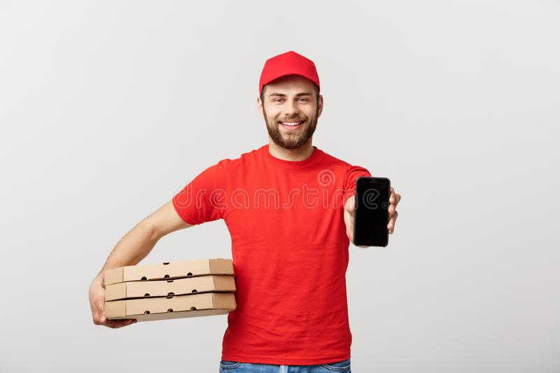 Pizza delivery man holding a mobile and pizza boxes over white background. Pizza delivery man holding a mobile and pizza boxes over white background royalty free stock photography