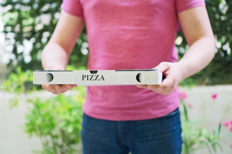 Pizza delivery man. Pizza delivery man holding pizza box royalty free stock photos
