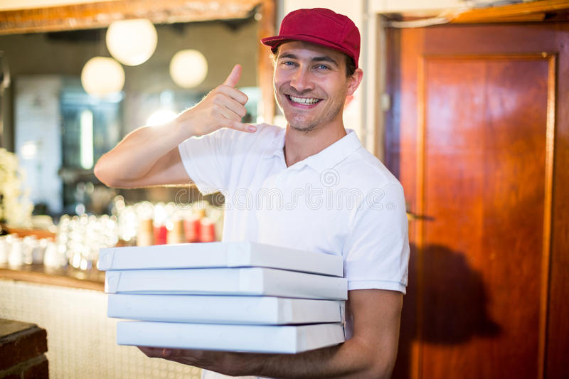 Pizza delivery man holding pizza boxes making a phone gesture. In restaurant stock images