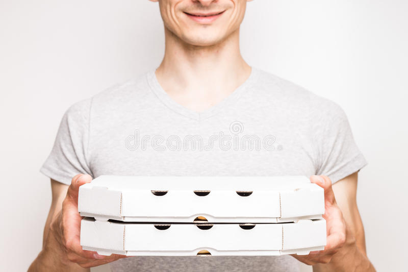 Pizza delivery man holds two boxes. Pizza delivery man in grey t-shirt holds two boxes with food stock image
