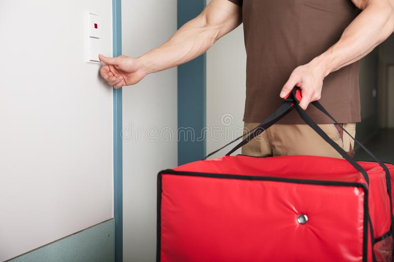 Pizza Delivery Man Ringing The Door Bell. With A Large Red Bag In His Hand royalty free stock image