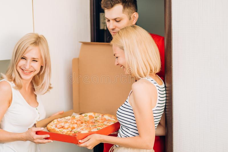 Two young caucasian woman receiving pizza from delivery man at home. Pizza delivery men brought order pizza to clients home. Two joyful young blonde women royalty free stock photo