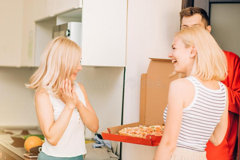 Two young caucasian woman receiving pizza from delivery man at home. Pizza delivery men brought order pizza to clients home. Two joyful young blonde women royalty free stock images