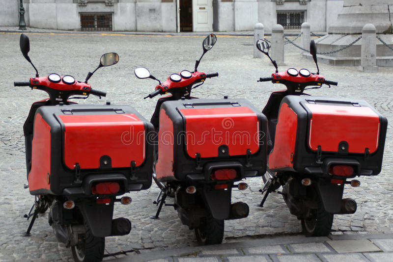 Pizza delivery scooters. Real street picture of three pizza delivery scooters standing on the street royalty free stock photo