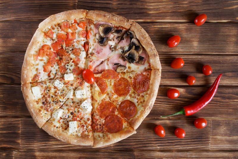 Pizza deliziosa con le merguez, salame, peperoncino rosso, prosciutto, funghi, formaggio, bugie del quattro-pezzo dei pomodori su fotografia stock