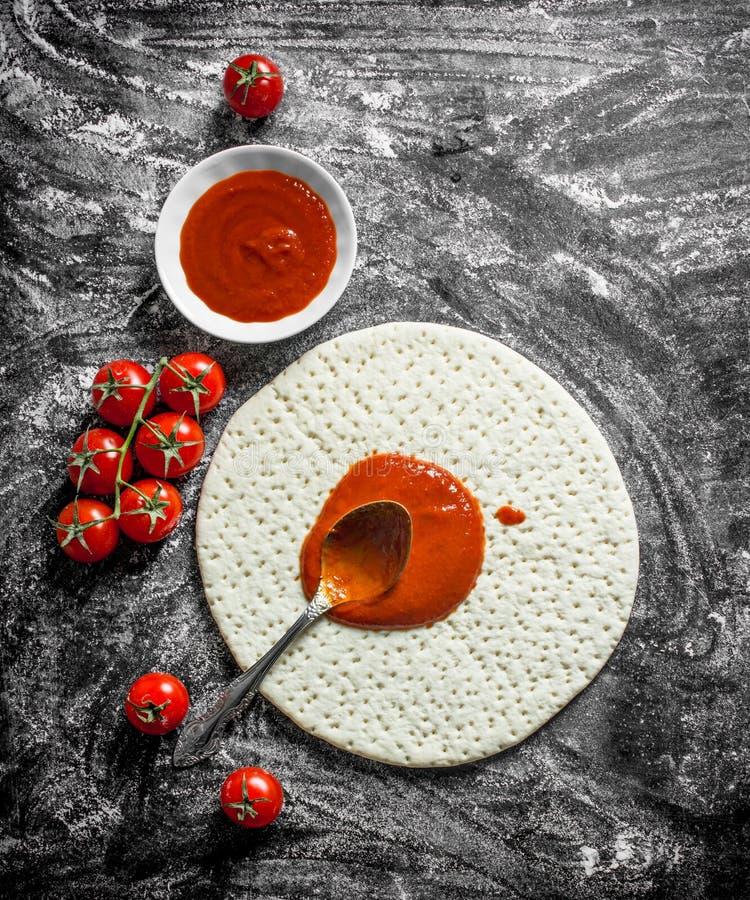 Pizza della preparazione Pasta srotolata con passata di pomodoro ed i pomodori freschi fotografia stock libera da diritti