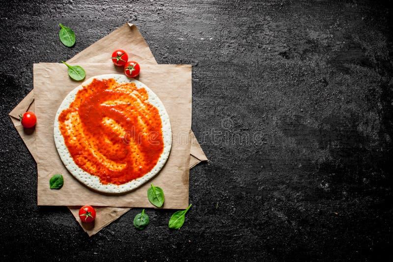 Pizza della preparazione Pasta srotolata con passata di pomodoro fotografia stock libera da diritti