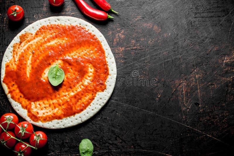 Pizza della preparazione Pasta srotolata con passata di pomodoro fotografia stock