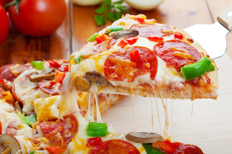 Pizza Deluxe. A slice of hot pizza deluxe with pepperoni, mushrooms, peppers, & lots of gooey mozzarella cheese, ready to be served stock image