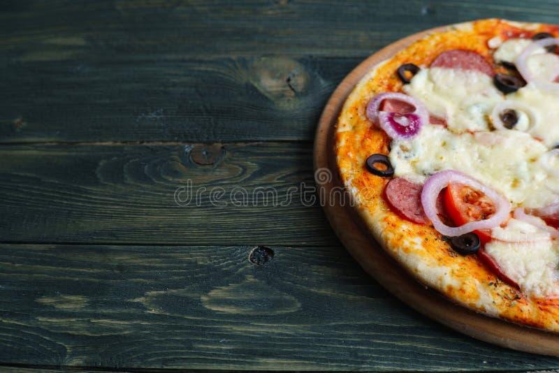 Pizza di merguez casalinga fresca con le olive e la cipolla sul legno fotografie stock