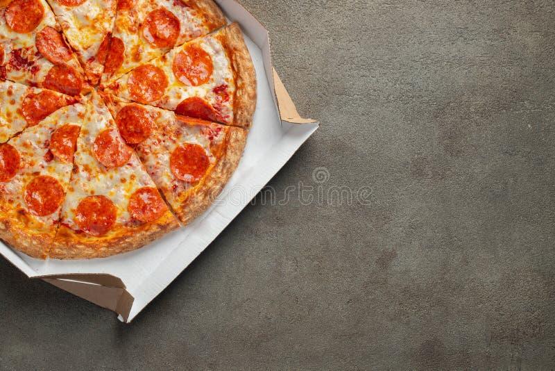Pizza di merguez saporita in una scatola su fondo concreto marrone Vista superiore della pizza di merguez calda Con lo spazio del fotografia stock