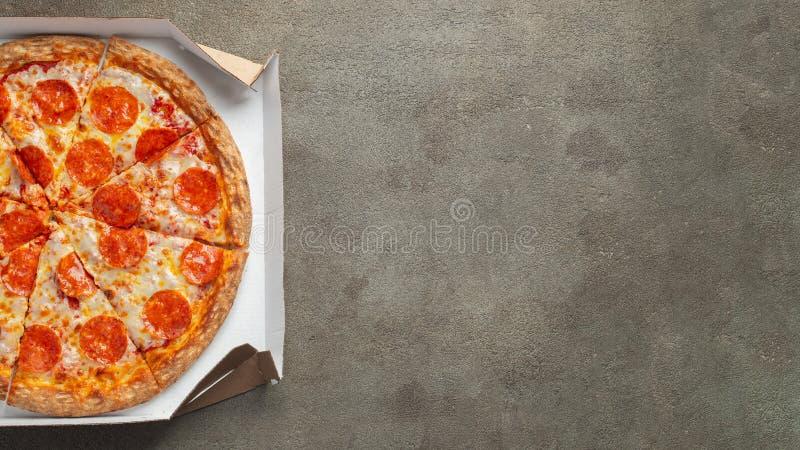 Pizza di merguez saporita in una scatola su fondo concreto marrone Vista superiore della pizza di merguez calda Con lo spazio del fotografie stock libere da diritti