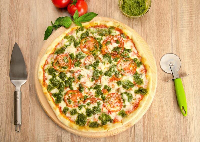Pizza di pesto con formaggio, i pomodori ed i capperi su un bordo di legno immagini stock