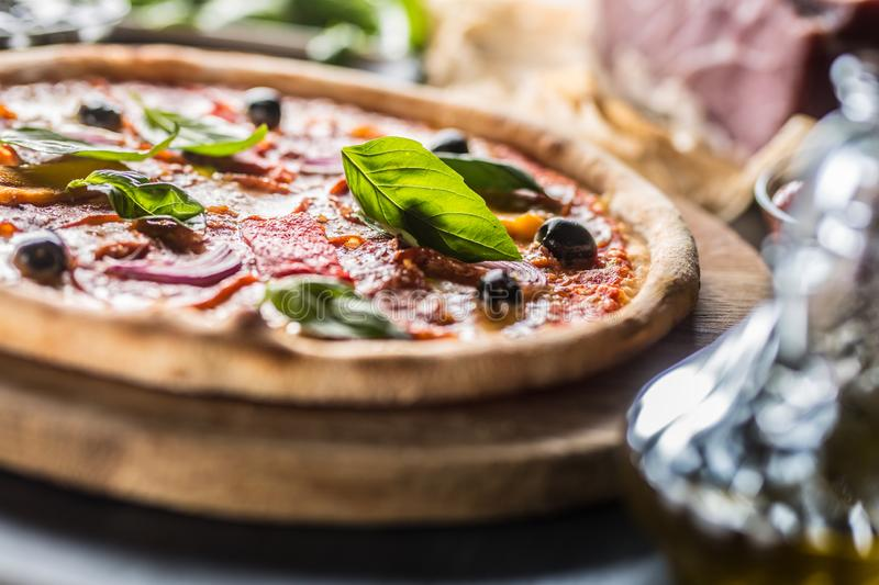 Pizza diavolo traditional italian meal from spicy salami peperoni chili onion olives and basil royalty free stock images
