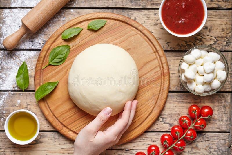 Pizza, die Bestandteile kocht Mozzarella, Tomaten, Basilikum, Olivenöl, Gewürze Arbeit mit dem Teig Beschneidungspfad eingeschlos lizenzfreies stockfoto