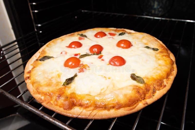 Pizza die close-up met tomaten en kaas van de oven maken stock fotografie