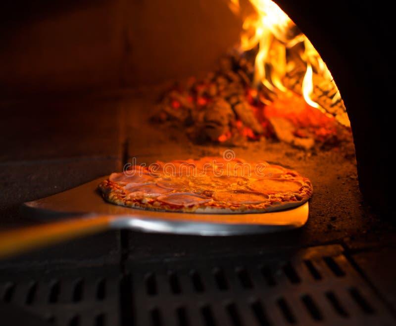 Pizza, die vom Ofen erhält lizenzfreie stockfotos