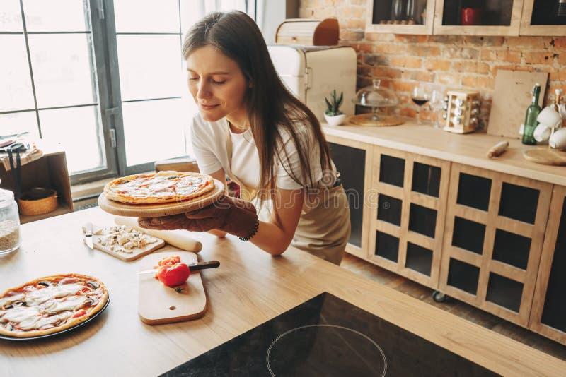 Pizza do cozimento da dona de casa da jovem mulher para sua família fotografia de stock